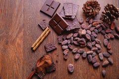 Barras de chocolate e chocolate pulverizado com feijões de cacau fotografia de stock