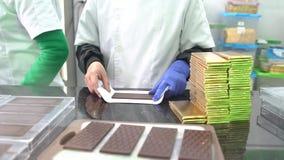Barras de chocolate de empacotamento nos envoltórios à mão na fábrica filme