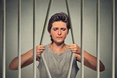 Barras de doblez subrayadas de la mujer triste desesperada de su celda de prisión Fotografía de archivo libre de regalías