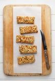 Barras de granola hechas en casa de la energía en tabla de cortar de madera con el cuchillo Foto de archivo libre de regalías