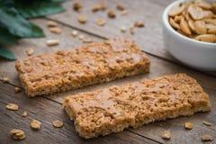 Barras de Granola na tabela e em amendoins de madeira na bacia foto de stock royalty free