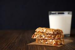 Barras de granola sanas en el pergamino con leche en la tabla de madera Imagen de archivo