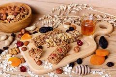 Barras de la aptitud con el granola, la harina de avena, las nueces, los frutos secos y la miel Foto de archivo