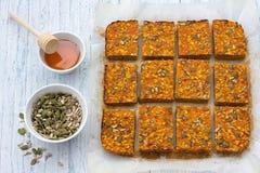 Barras de la zanahoria con la harina de avena, los albaricoques secados, las semillas y la miel Imagen de archivo