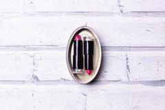 Barras de labios conservadas rojas en la pared foto de archivo libre de regalías