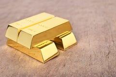 Barras de ouro brilhantes na tabela imagens de stock royalty free
