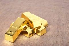 Barras de ouro brilhantes na tabela imagens de stock