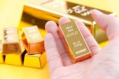 Barras de ouro da posse da mão fotografia de stock