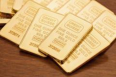 Barras de ouro na superfície da madeira imagens de stock