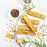 Barras de pan de la pasta de hojaldre con las semillas del lino y de sésamo en un fondo ligero con romero Visión superior Fotos de archivo