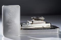 Barras de prata e moedas Minted contra um fundo cinzento fotografia de stock royalty free