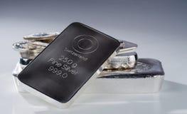 Barras de prata e moedas Minted contra um fundo do cinza azul fotografia de stock royalty free