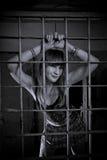 Barras de trás fechados da moça, grade, como na prisão vista 'sexy' na saia curto fotos de stock