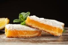 Barras deliciosas da torta do limão no fundo escuro fotografia de stock royalty free