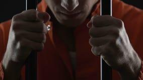 Barras deprimidas de la célula de tenencia del preso y pensamiento en el crimen confiado, pesar almacen de metraje de vídeo
