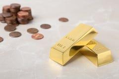 Barras e moedas de ouro na tabela foto de stock
