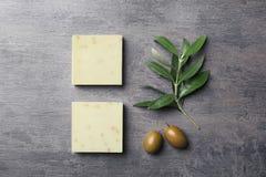 Barras feitos a mão e folhas do sabão com azeitonas no fundo cinzento fotografia de stock royalty free