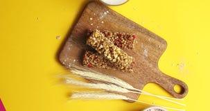 Barras y avena del cereal en el tablero de madera almacen de video