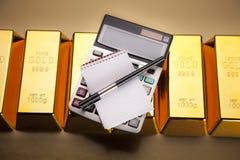 Barras y calculadora de oro fotos de archivo libres de regalías