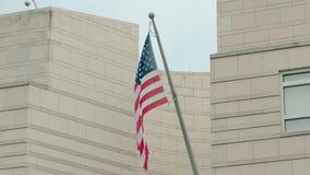 Barras y estrellas de la bandera de América de la cámara lenta en el edificio de la embajada de los E.E.U.U. en Berlín, Alemania  almacen de metraje de vídeo