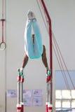 Barrases paralelas competentes del varón de los gimnastas Foto de archivo