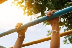 Barre accrochante de petit garçon par 2 mains l'équipement extérieur d'exercice Image libre de droits