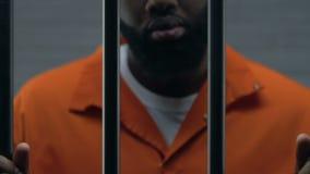 Barre afroamericane pericolose della prigione della tenuta del criminale, imprigionamento, primo piano archivi video