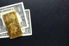 Barre de billet de banque et d'or Images stock
