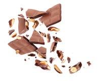 Barre de chocolat avec nuts divisée en morceaux dans le ciel sur un blanc photographie stock libre de droits