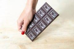 Barre de chocolat dans une main femelle avec une manucure lumineuse Fond en bois Colorsde Light Photographie stock libre de droits