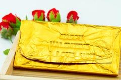 Barre de chocolat enveloppée dans un or Ford Dactylographiez le pressurage de lettres Images libres de droits