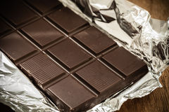 Barre de chocolat foncée dans l'emballage ouvert d'aluminium Photographie stock