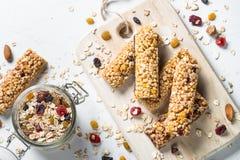 Barre de granola avec les écrous, le fruit et les baies sur le blanc Photographie stock