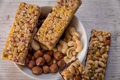 Barre del cereale disposte su una tavola con gli additivi del dado fotografia stock libera da diritti