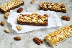 Barre di granola sane con i dadi, i semi ed i frutti secchi sulla tavola grigia di struttura, con lo spazio della copia Fotografie Stock Libere da Diritti