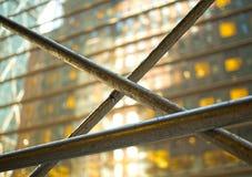 Barre di metallo davanti ad una costruzione di vetro con le finestre d'ardore gialle Fotografie Stock Libere da Diritti