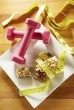 Barre di muesli del cioccolato con nastro adesivo e pesi di misurazione Fotografie Stock