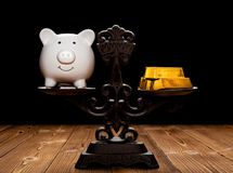 Barre di oro e del porcellino salvadanaio su una scala equilibrata immagini stock libere da diritti