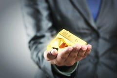 Barre dorate sulla mano della donna Fotografie Stock
