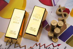 Barre e monete di oro sui diagrammi! Immagini Stock