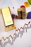 Barre e soldi di oro sui diagrammi! Immagine Stock