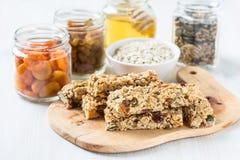 Barre ed ingredienti di granola casalinghi sani su fondo Fotografia Stock