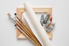 Barre en bois de civière, pinceaux, rouleau de toile d'artiste et tubes de peinture Photo stock
