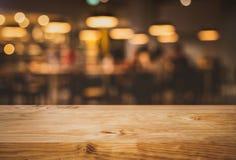 Barre en bois de compteur de dessus de table de texture avec le bokeh léger d'or de tache floue en café, fond de restaurant Pour  photos libres de droits