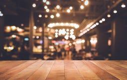 Barre en bois de dessus de table avec le bokeh de lumière de tache floue en café foncé de nuit Image stock