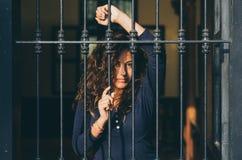 Barre indietro chiuse della ragazza, rete, come in prigione immagini stock libere da diritti