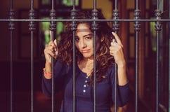 Barre indietro chiuse della ragazza, rete, come in prigione fotografia stock