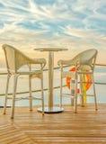 Barre la tabla y dos taburetes de bar en la cubierta en la puesta del sol Fotos de archivo libres de regalías