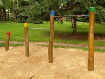 Barre orizzontali d'acciaio sulle colonne di legno nel campo da giuoco dei bambini Sabbia arancio sotto le barre Fotografia Stock Libera da Diritti