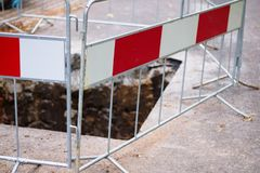 Barred access. Metal fence barring access to hole in concrete pavement with a hole Stock Image